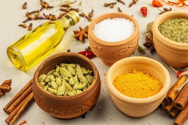 Um conjunto de especiarias para cozinhar curry. condimentos aromáticos: açafrão, páprica, cardamomo, canela, anis estrelado, pimentão, pimenta-do-reino, ervas secas, sal. fundo de concreto de pedra clara, close-up