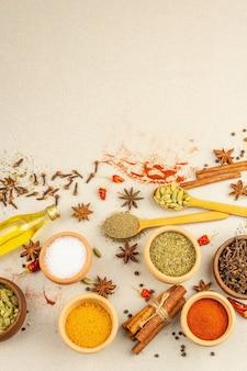 Um conjunto de especiarias para cozinhar curry. condimentos aromáticos: açafrão, páprica, cardamomo, canela, anis estrelado, pimentão, pimenta-do-reino, ervas secas, sal. fundo de concreto de pedra clara, vista superior
