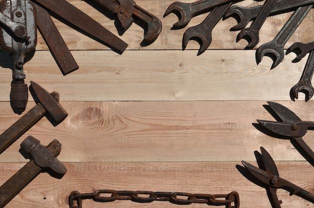 Um conjunto de ferramentas antigas e enferrujadas encontra-se em uma mesa de madeira na oficina