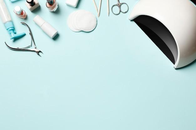 Um conjunto de ferramentas cosméticas para manicure e pedicure em um fundo azul. esmaltes de gel, limas de unha e cortadores e a vista superior da lâmpada local para texto. vista do topo. postura plana
