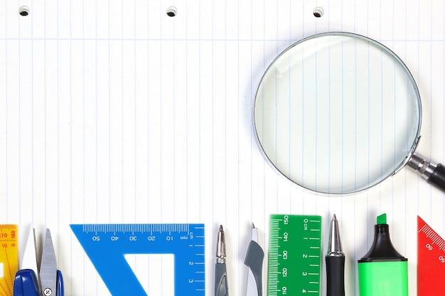 Um conjunto de ferramentas de escritório no caderno para fazer anotações. moldura para registros e lupa.
