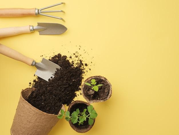 Um conjunto de ferramentas de jardinagem em uma parede amarela. a terra escorre da panela. vista de cima. lugar para o seu texto. copie o espaço.