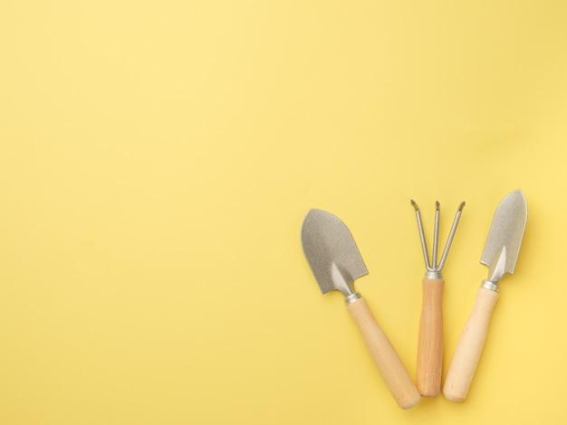 Um conjunto de ferramentas de jardinagem em uma parede amarela. vista de cima. lugar para o seu texto. copie o espaço.