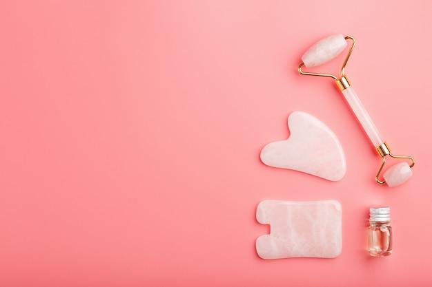 Um conjunto de ferramentas para a técnica de massagem facial gua sha, feita de quartzo rosa natural em um fundo rosa. rolo, pedra de jade e óleo em uma jarra de vidro para cuidar do rosto e do corpo.