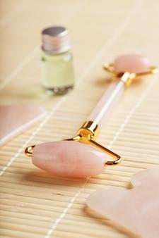 Um conjunto de ferramentas para a técnica de massagem facial gua sha, feita de quartzo rosa natural. rolo, pedra de jade e óleo em uma jarra de vidro, sobre um fundo de palha para cuidados com o rosto e o corpo.
