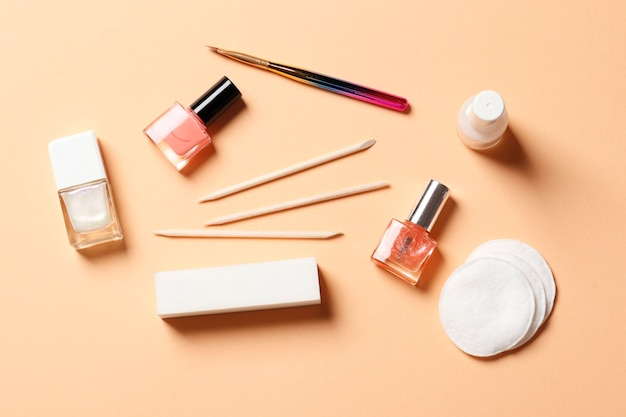 Um conjunto de ferramentas para manicure e esmalte em um fundo rosa