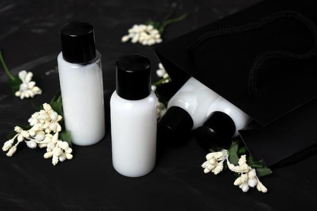 Um conjunto de frascos com shampoo cosméticos para pele e cabelos em um fundo escuro com flores brancas.
