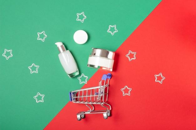 Um conjunto de frascos cosméticos brancos encontra-se em uma cesta em um fundo verde e vermelho brilhante. compras online para casa. o conceito de compra de cosméticos, compras online, férias