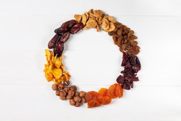Um conjunto de frutas secas, frutas e nozes sob a forma de uma coroa de flores (avelã, abóbora, cereja, damasco, maçã, datas)