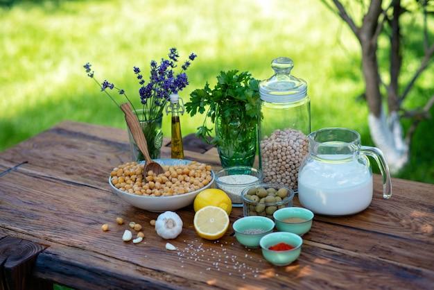 Um conjunto de ingredientes para a preparação de salgadinhos de hummus: grão de bico, tahine, especiarias, alho, salsa, azeite de oliva em uma mesa de madeira.