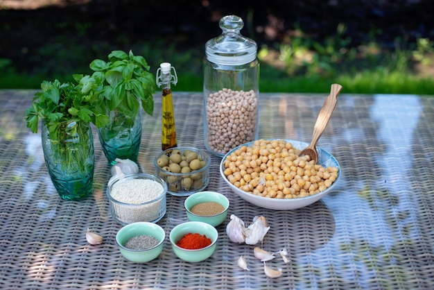 Um conjunto de ingredientes para a preparação de salgadinhos de hummus: grão de bico, tahine, especiarias, alho, salsa, azeite de oliva.