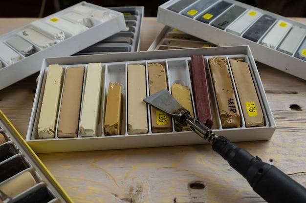 Um conjunto de lápis de cera e um ferro de solda para consertar lascas e arranhões em superfícies de madeira.
