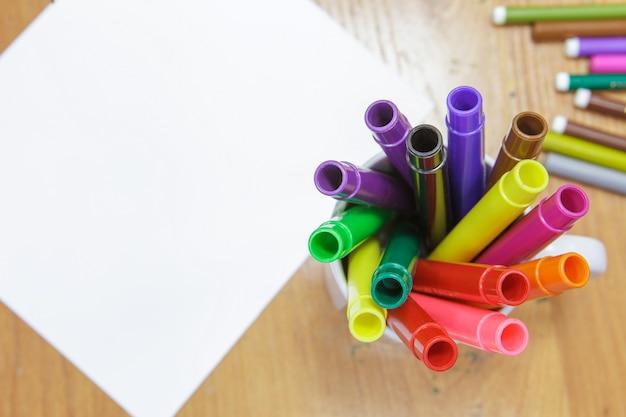Um conjunto de marcadores coloridos e uma folha de papel branco em cima da mesa.
