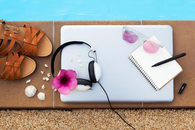 Um conjunto de objetos de viagem freelancer hipster deitado na piscina, estilo verão feminino, um laptop, fones de ouvido, sandálias, livro de diário de viagem, caneta, óculos de sol, vista de cima, flatlay