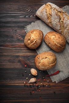 Um conjunto de pão, pimenta, alho em uma placa de madeira marrom