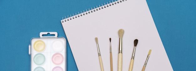 Um conjunto de pincéis, um caderno e aquarelas brilhantes sobre um fundo azul, o conceito de criatividade