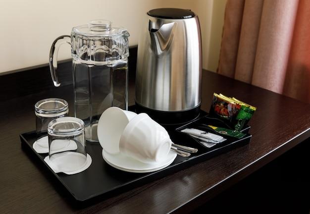 Um conjunto de pratos em uma bandeja preta para chá e café. bule, jarro de vidro, copos de vidro, xícaras. a mesa é de madeira escura. hotel, casa.