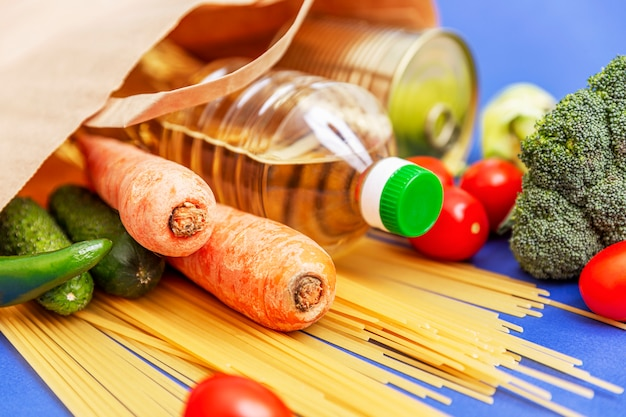 Um conjunto de produtos em uma sacola ecológica de papel no canto do quadro. mistura de legumes frescos, garrafas com óleo vegetal e alimentos enlatados. entrega durante a pandemia de coronavírus.