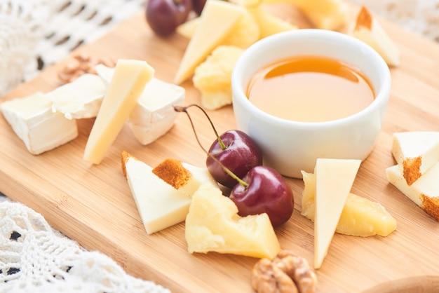 Um conjunto de queijo parmesão, mussarela, camembert e uma xícara de azeite em uma placa de madeira