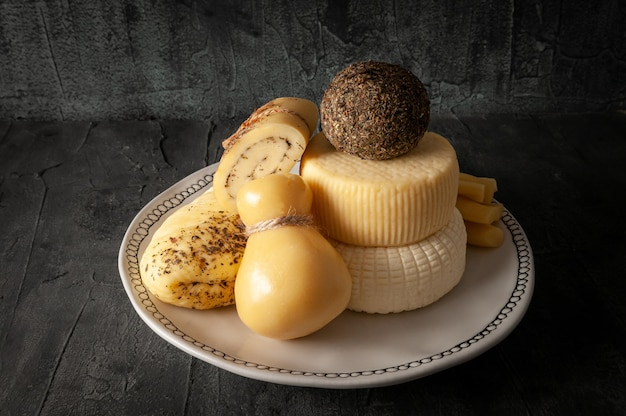 Um conjunto de queijos. halumi, caciotta, caciocavallo, palitos de queijo, suluguni, belper knolle, pão de queijo com ervas provençais. em uma placa de cerâmica branca. fundo escuro. fechar-se.
