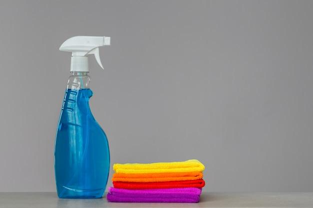 Um conjunto de roupas de limpeza coloridas e um agente de limpeza em frasco de spray azul.