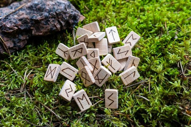 Um conjunto de runas escandinavas feitas em dados de madeira encontra-se em um musgo natural. ferramenta de previsão do futuro, conceito de previsão do futuro.