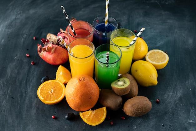 Um conjunto de sumos frescos frescos espremidos ou cocktails em um copos feitos de laranja, kiwi, limão, uvas, romãs