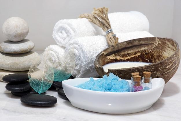 Um conjunto de tratamentos de spa com leite de coco, pedras quentes e sal de banho azul está localizado em uma bancada de mármore branco.