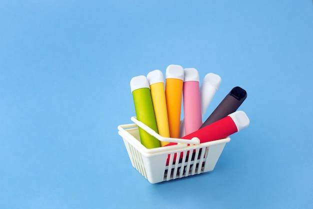 Um conjunto de varas multicoloridas - dispositivos de vaporização descartáveis, cigarros eletrônicos em uma cesta de compras em uma superfície azul.