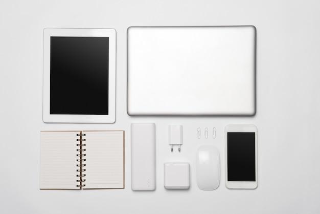 Um conjunto minimalista de acessórios empresariais brancos e dispositivos digitais