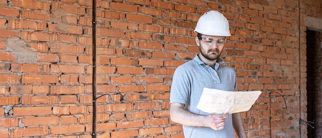 Um construtor com roupas de trabalho examina um desenho de construção em um canteiro de obras