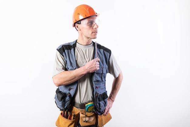 Um construtor em um capacete faz medições visuais com um lápis de marcação. para qualquer propósito.