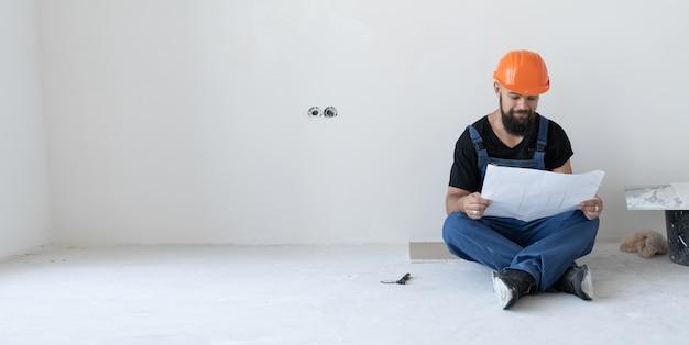 Um construtor masculino brutal está sentado no chão. vestido com um uniforme azul e uma máscara laranja. ele segura uma folha velha e surrada com desenhos nas mãos. lugar para texto.