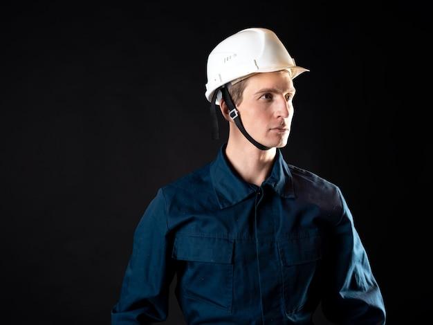 Um construtor ou reparador, um homem com uma túnica e um capacete protetor