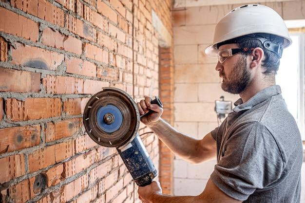 Um construtor profissional de roupas de trabalho trabalha com uma ferramenta de corte