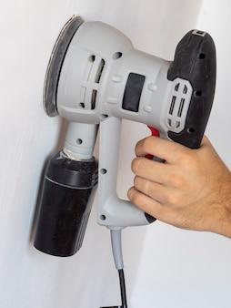 Um construtor usa uma lixadeira para processar uma parede de concreto branco. show de construção