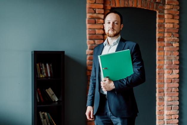 Um contador adulto e bem sucedido em um terno está de pé e segurando uma pasta verde