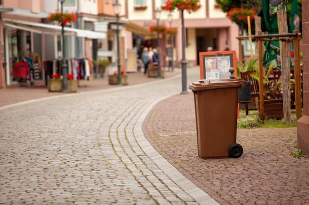 Um contêiner de lixo fica na rua de uma cidade alemã europeia. a rua é pavimentada com paralelepípedos.