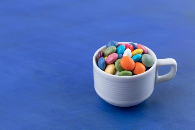 Um copo branco cheio de doces na superfície azul