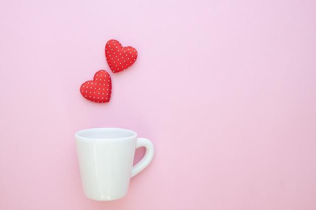Um copo branco com bolinhas corações vermelhos em fundo rosa