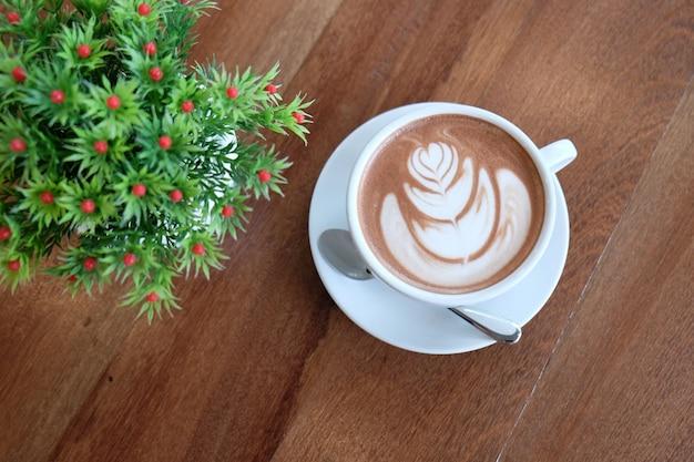 Um copo branco de cacau quente bonito na mesa de madeira