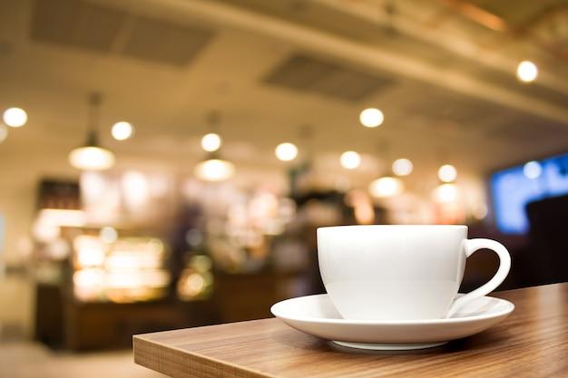 Um copo branco na mesa de madeira com café borrão de fundo