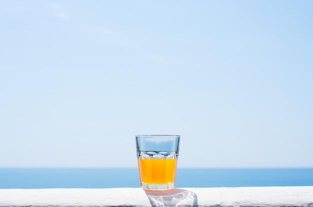 Um copo cheio de suco contra o pano de fundo do mar