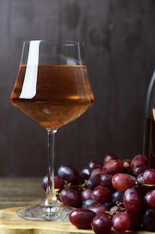 Um copo cheio de vinho rosé e um cacho de uvas vermelhas estão próximos. fechar-se. orientação vertical