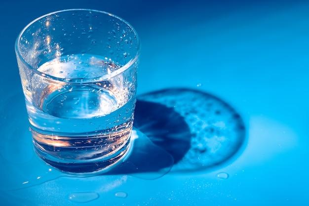 Um copo com água cai sobre um azul escuro close-up