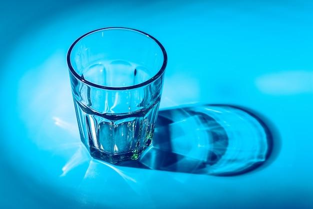 Um copo com água cai sobre uma mesa azul escura