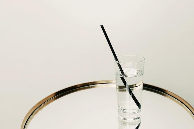 Um copo com água e palha