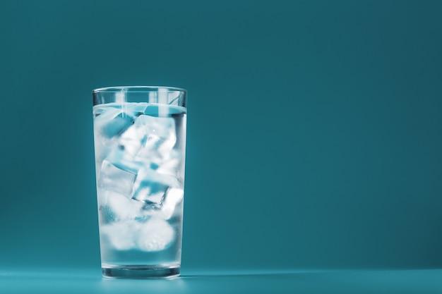 Um copo com água gelada e cubos de gelo em uma superfície azul