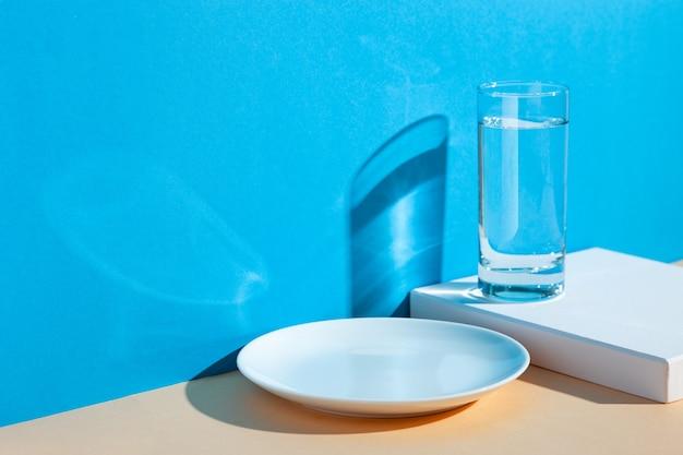 Um copo com água, limão e laranja