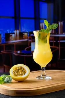 Um copo com bebida de maracujá em uma placa de madeira começa na fruta ao lado do copo